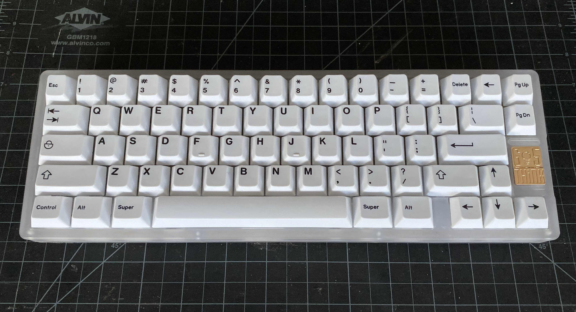 Frosted polycarb, gold PVD badge, GMK Minimal from Discord user sandrasays!